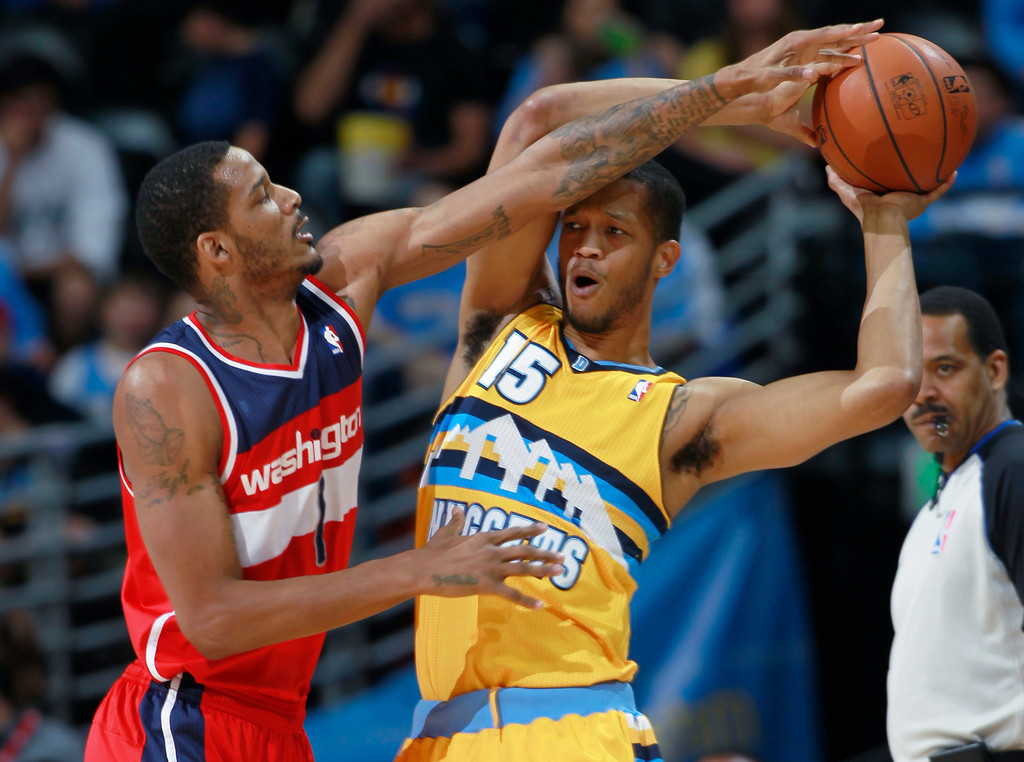 . Washington Wizards forward Trevor Ariza, left, reaches for ball as Denver Nuggets forward Anthony Randolph looks to pass in the first quarter of an NBA basketball game, Sunday, March 23, 2014, in Denver. (AP Photo/David Zalubowski)