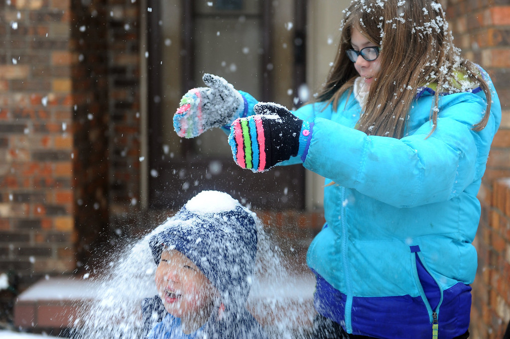 . Olivia Aurs, 9, dumps a handful of snow on her three year-old brother, Alex Aurs\' head as they play in the snow in the Lakeside Terrace subdivision in Evansville, Ind. on Friday morning, Dec. 6, 2013.  Alex was adopted from China last year by the family, and this was his very first experience with snow. (AP Photo/The Evansville Courier & Press, Erin McCracken)