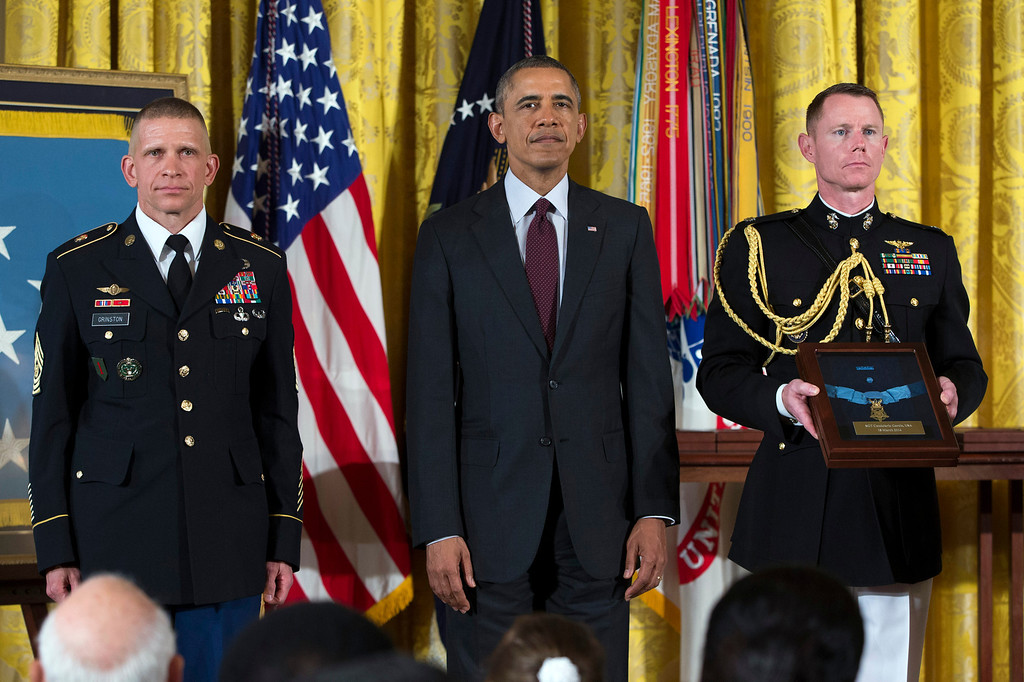 . Command Sgt. Major Michael Grinston, left, stands with President Barack Obama before accepting the Medal of Honor on behalf of Sgt. Candelario Garcia during a ceremony in the East Room of the White House on Tuesday, March 18, 2014, in Washington. Obama awarded 24 Army veterans the Medal of Honor for conspicuous gallantry in recognition of their valor during major combat operations in World War II, the Korean War and the Vietnam War. (AP Photo/ Evan Vucci)