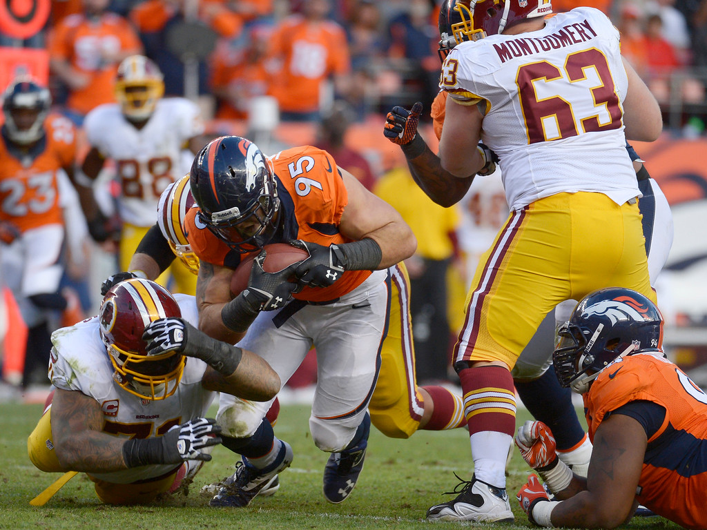 . Denver Broncos defensive end Derek Wolfe (95) picks up a ball fumbled by Washington Redskins quarterback Robert Griffin III (10) during the fourth quarter.   (Photo by Tim Rasmussen/The Denver Post)