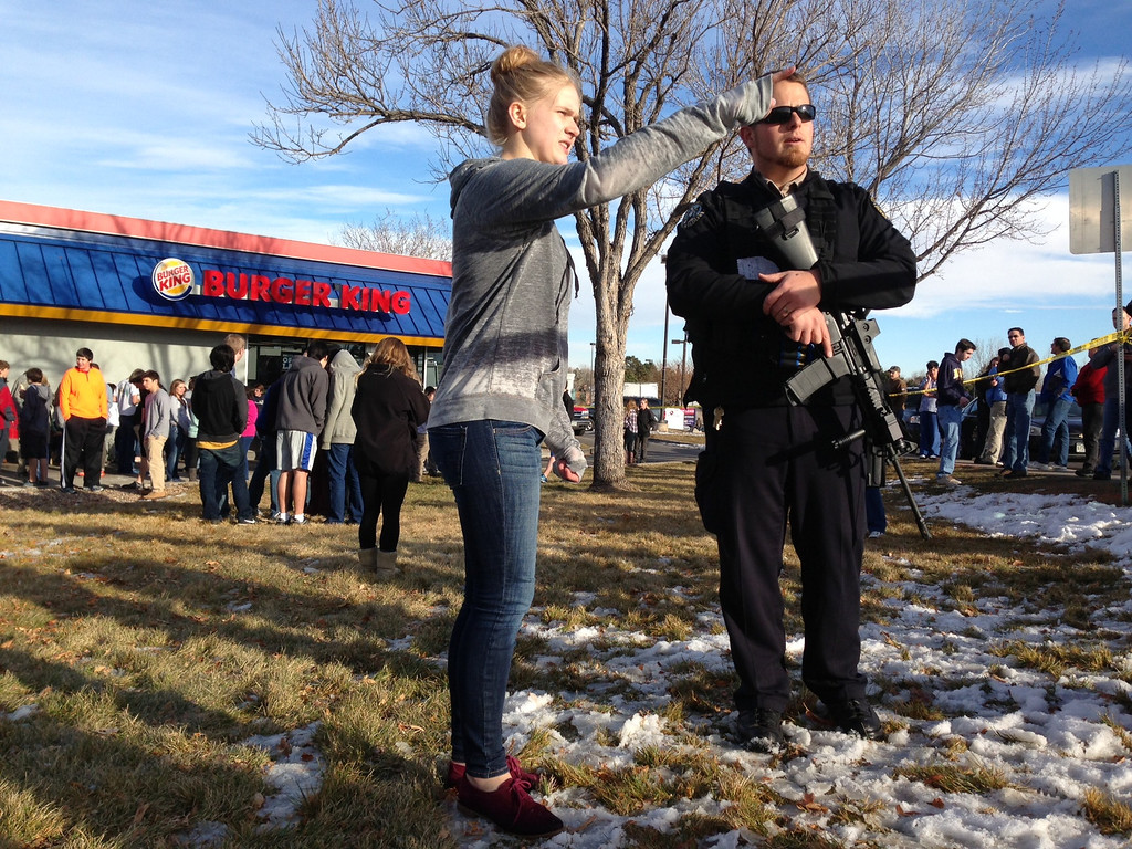 . Emergency personnel, students and bystanders congregate outside a Burger King restaurant near  Arapahoe High School in Centennial, Colo. after gun shots were reportedly fired inside the school on Friday afternoon, Dec. 13, 2013. (Photo by Craig F. Walker/The Denver Post)