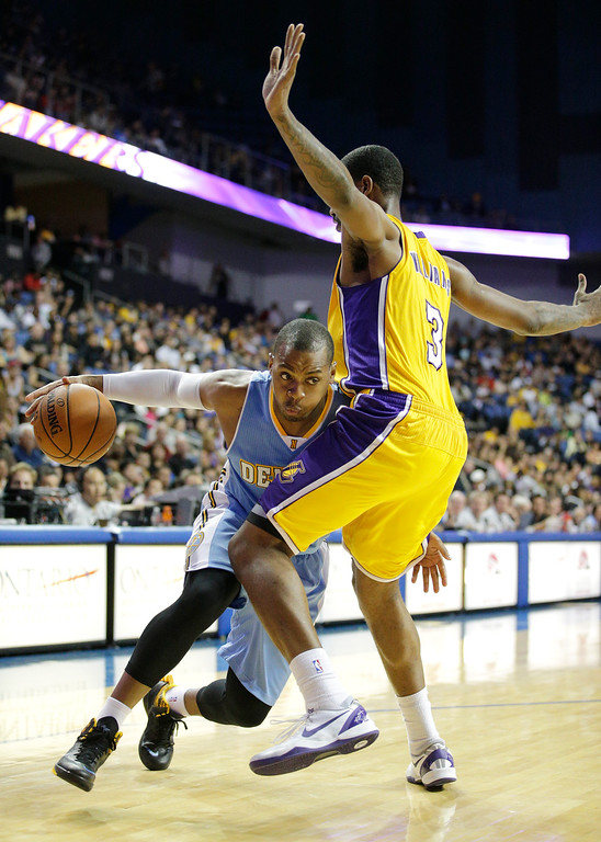 . Denver Nuggets\' Randy Foye, left, is defended by Los Angeles Lakers\' Shawne Williams in the second half of an NBA preseason basketball game on Tuesday, Oct. 8, 2013, in Ontario, Calif. The Lakers won 90-88. (AP Photo/Jae C. Hong)