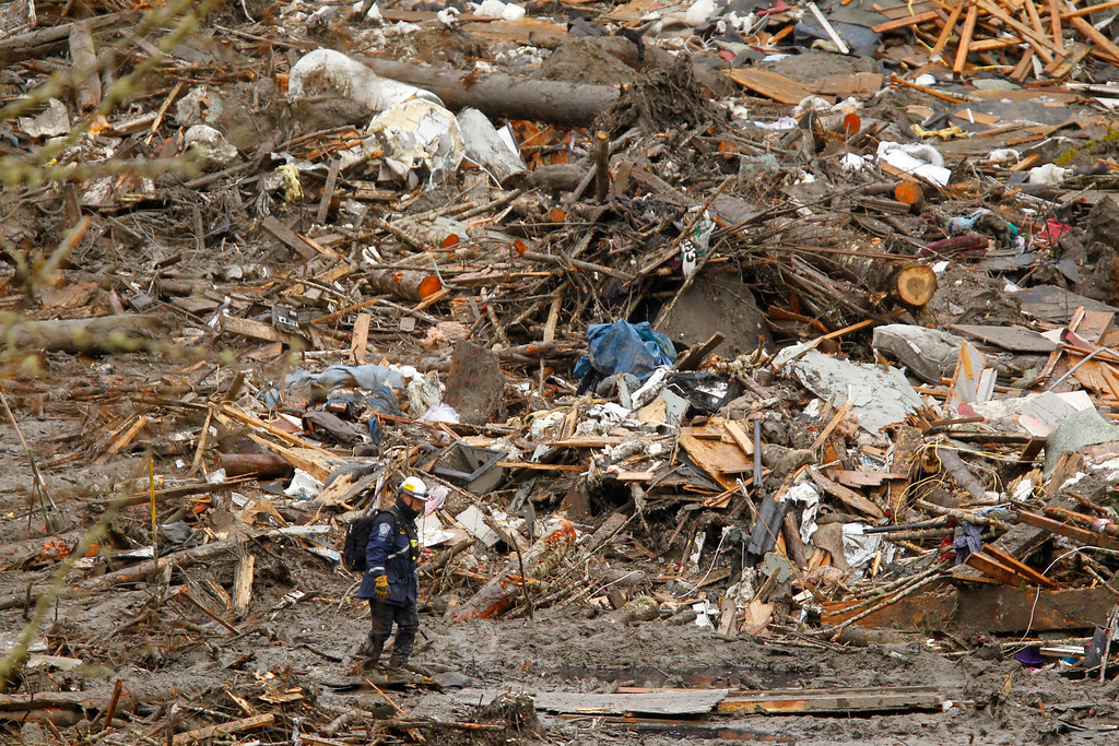 . A searcher walks in front of a massive pile of debris at the scene of a deadly mudslide, Thursday, March 27, 2014, in Oso, Wash.  (AP Photo/The Herald, Mark Mulligan, Pool)