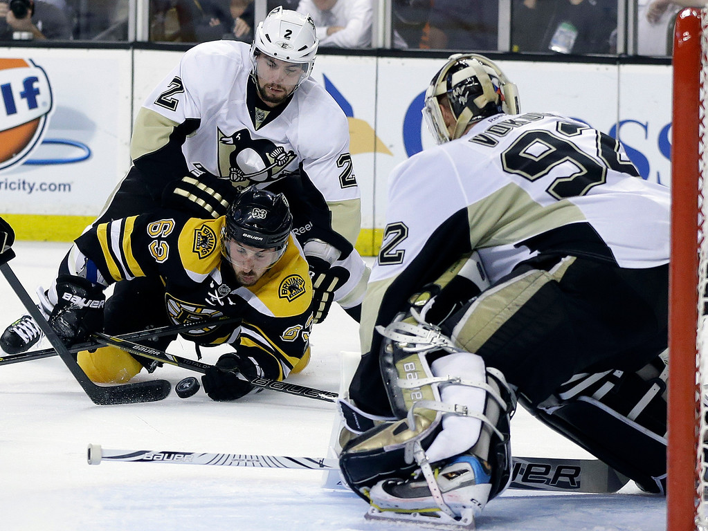. Pittsburgh Penguins defenseman Matt Niskanen, rear, defends against Boston Bruins left wing Brad Marchand (63), who tries to gain the puck in front of Penguins goalie Tomas Vokoun (92) during the second period of Game 4 in the Eastern Conference finals of the NHL hockey Stanley Cup playoffs, in Boston on Friday, June 7, 2013. (AP Photo/Elise Amendola)