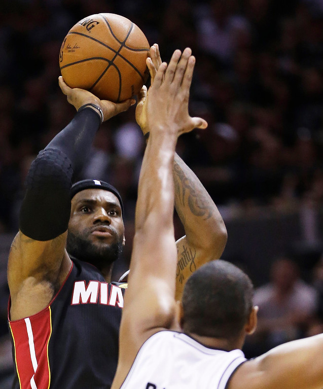 . Miami Heat forward LeBron James shoots over San Antonio Spurs forward Boris Diaw during the first half in Game 5 of the NBA basketball finals on Sunday, June 15, 2014, in San Antonio. (AP Photo/David J. Phillip)