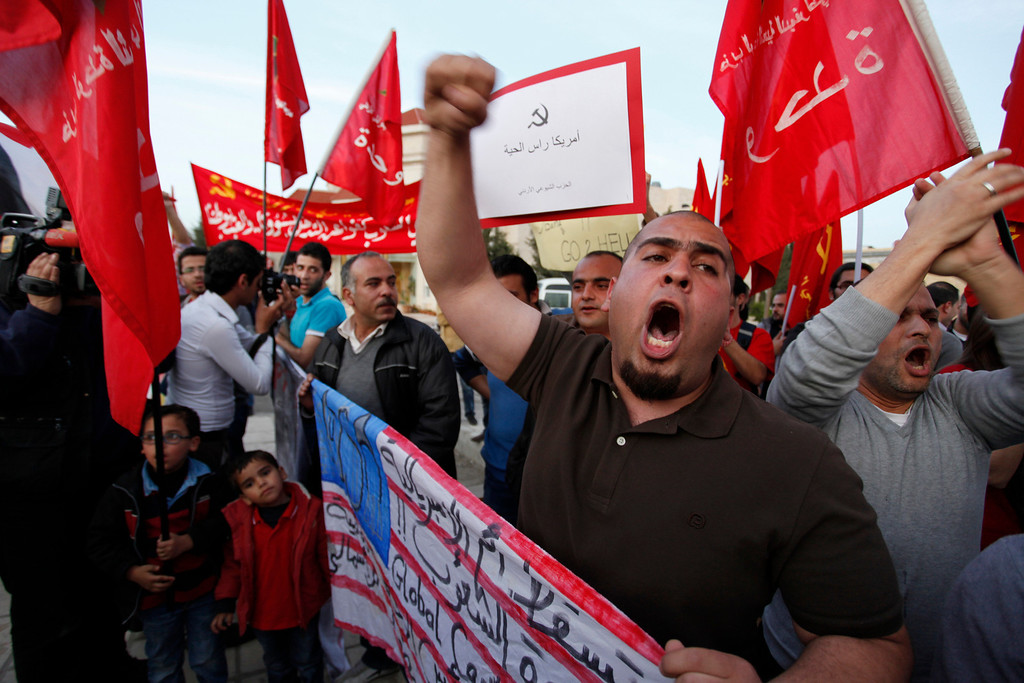 ". Activists from the Jordanian Communist Party and other parties, chant anti-U.S. slogans, during a protest in front of the U.S. embassy against the upcoming visit by President Barack Obama to the kingdom, in Amman, Jordan, Thursday, March 21, 2013.  Arabic on the U.S. flag reads, ""down with the mother of all imperialisms, the enemy of people, the head of the backward and the torture.\""  (AP Photo/Mohammad Hannon)"