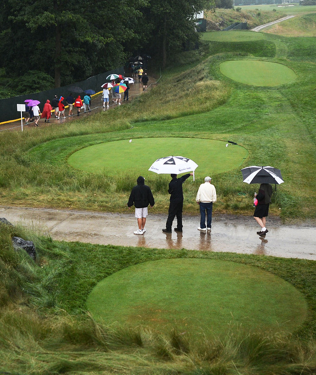 . A rain delayed part of the first round of the 113th US Open Golf Championship, at Merion Golf Club in Haverford.  Spectators walk with umbrellas near the 18th hole as the storms roll through. Photo by Tom Kelly IV Daily Local News