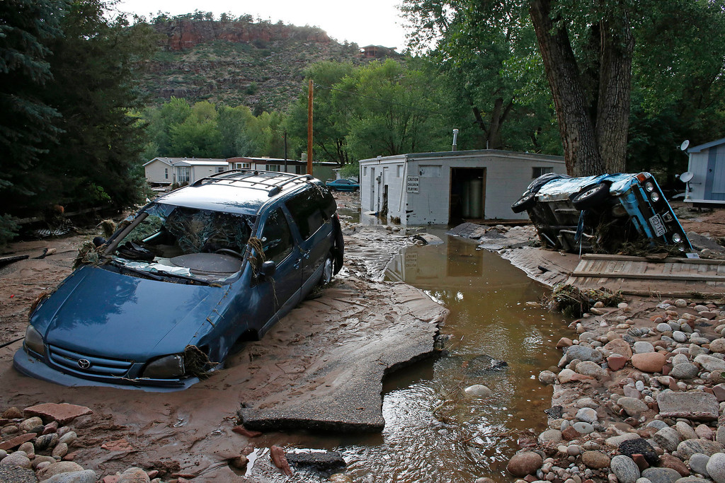 . Cars lay mired in mud deposited by floods in Lyons, Colo., Friday Sept. 13, 2013.  (AP Photo/Brennan Linsley)