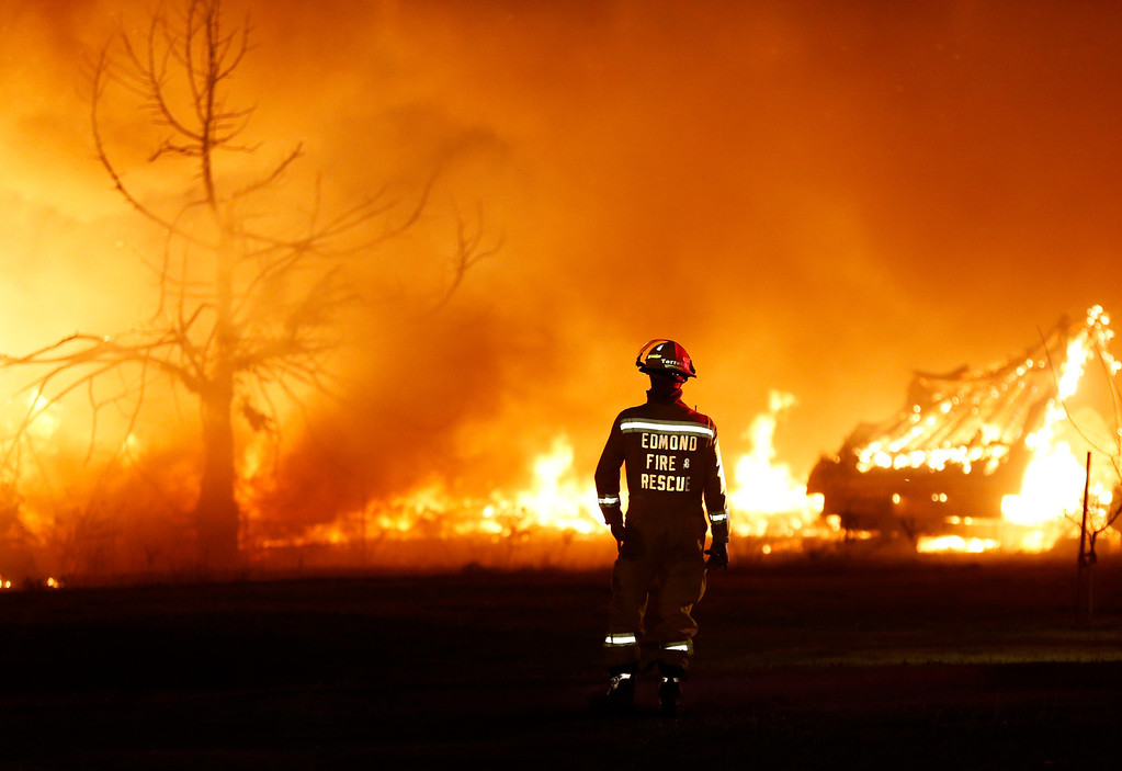 . An Edmond firefighter looks at a fire raging in a mobile home park near Prairie Grove Rd. and Douglas during Oklahoma wildfires in Logan County, Sunday, May 4, 2014.  Firefighters worked through the night and into early Monday to battle the large wildfire that destroyed at least six homes and left at least one person dead after a controlled burn spread out of control in central Oklahoma. (AP Photo/The Oklahoman, Nate Billings)