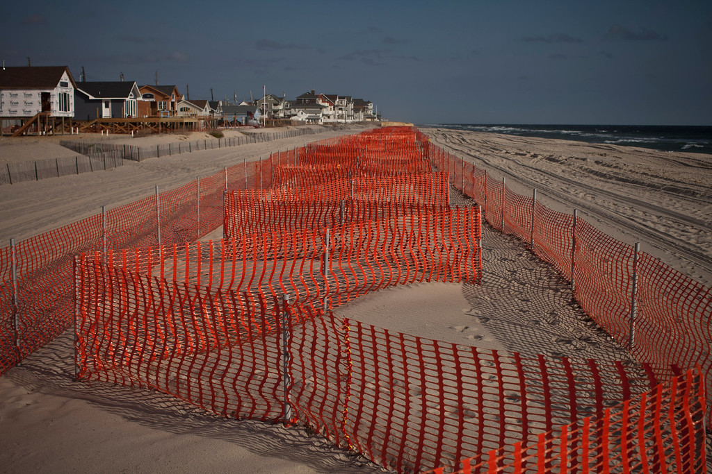 . Sand dunes are marked off as houses along the beachfront remain under construction one year after being partially destroyed by Superstorm Sandy, October 29, 2013 in Dover Beach North, New Jersey. (Photo by Kena Betancur/Getty Images)