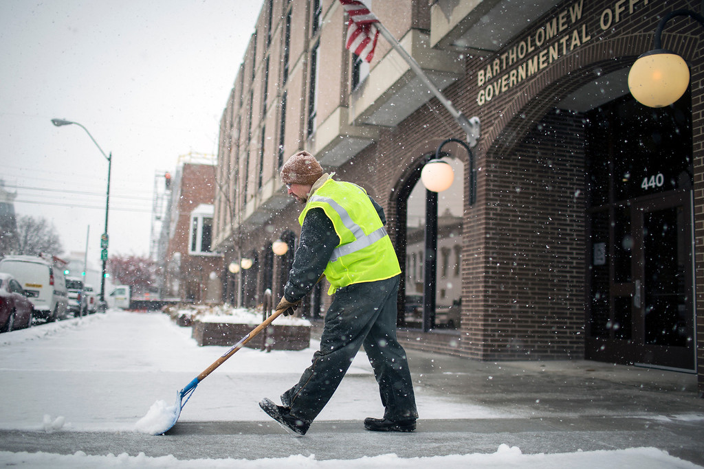 . Jason Rice clears snow in front of the Bartholemew County Governmental Office on Friday, Dec. 6, 2013 in downtown Columbus, Ind.  The overnight winter storm brought snow and ice to the region, and a winter storm warning that continues throughout the day. (AP Photo/The Republic, Chet Strange)