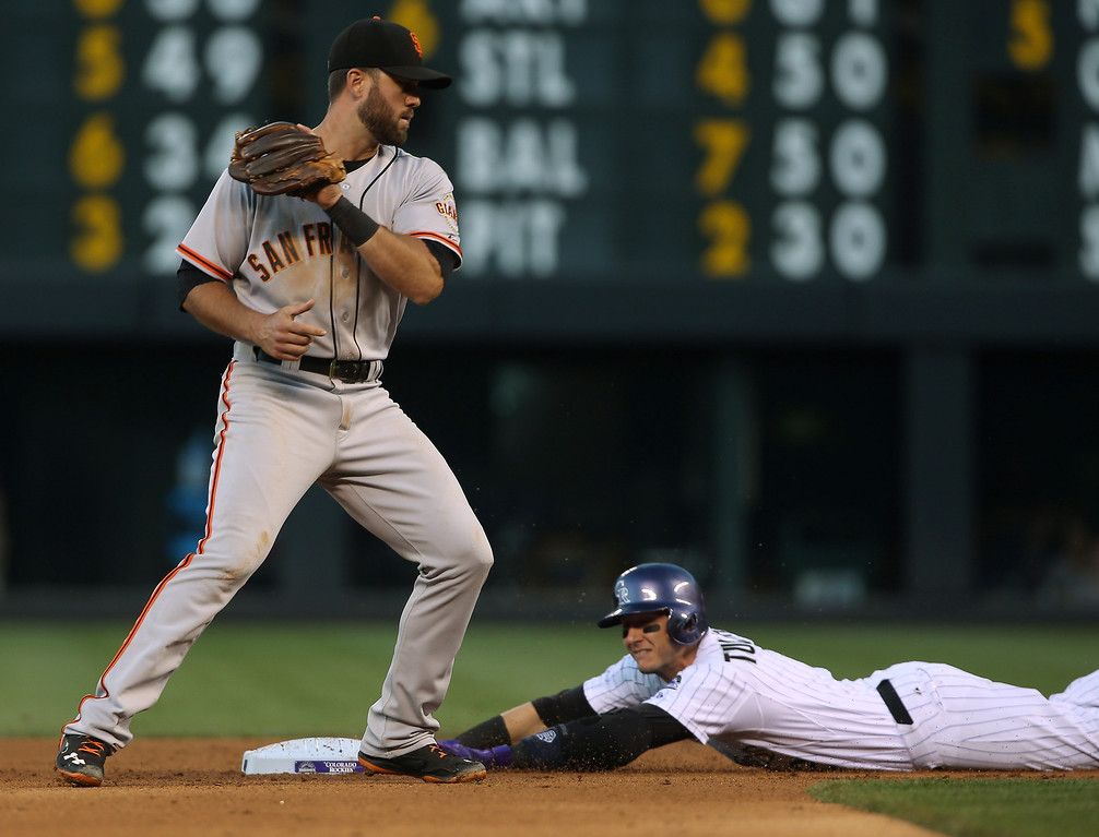 . San Francisco Giants second baseman Brandon Hicks, left, fields the throw as Colorado Rockies\' Troy Tulowitzki slides safely into second base with a double in the fourth inning of a baseball game in Denver on Tuesday, May 20, 2014. (AP Photo/David Zalubowski)