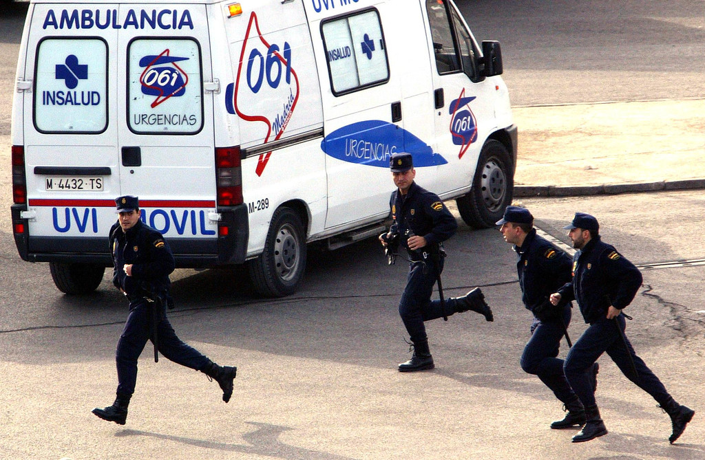 . Police officers run after an alert near the Atocha train station in Madrid 11 March 2004. At least 131 people were killed and some 400 injured early 11 March 2004 in near-simultaneous explosions on three trains in Madrid at the height of morning commuter traffic, the Spanish interior ministry said. In what appeared to be a deliberate attack staged only 72 hours ahead of Spanish general elections, the blasts went off on a long-distance high-speed carrier and two suburban trains packed with commuters. CHRISTOPHE SIMON/AFP/Getty Images