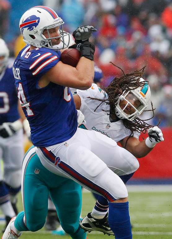 . Buffalo Bills tight end Scott Chandler (84) makes a catch as he is hit by Miami Dolphins outside linebacker Philip Wheeler (52) during the first half of an NFL football game Sunday, Dec. 22, 2013, in Orchard Park, N.Y. (AP Photo/Bill Wippert)