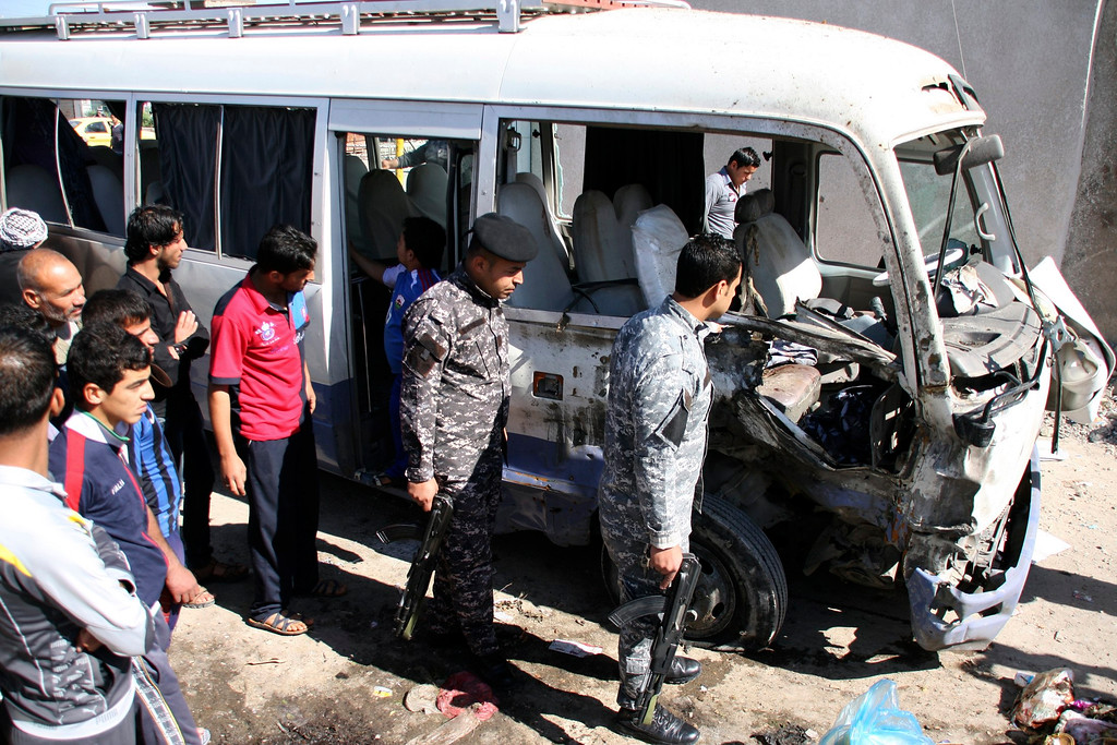 . Iraqi policemen and residents gather at the site of a car bomb attack in Baghdad\'s Sadr City March 19, 2013. A  REUTERS/Wissm al-Okili