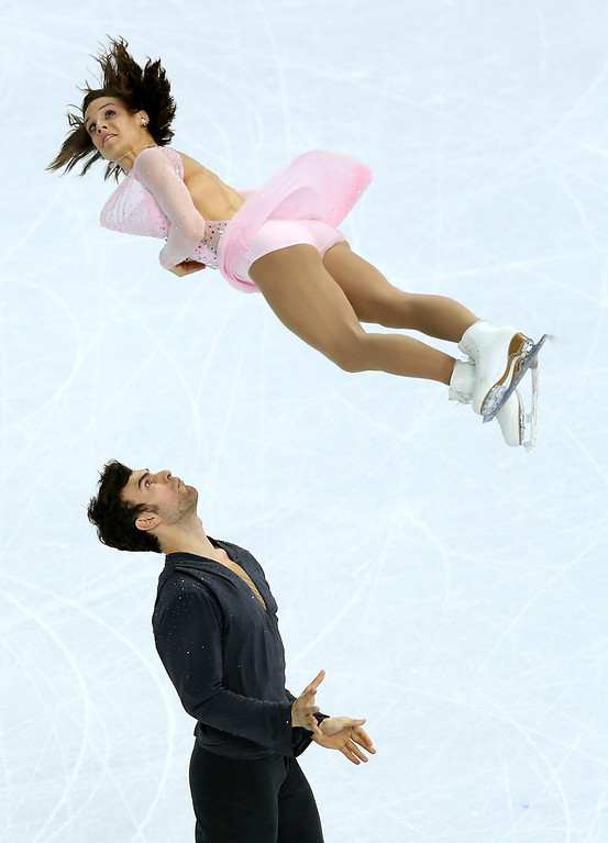 Description of . Meagan Duhamel and Eric Radford of Canada compete during the Figure Skating Pairs Short Program on day four of the Sochi 2014 Winter Olympics at Iceberg Skating Palace on February 11, 2014 in Sochi, Russia.  (Photo by Matthew Stockman/Getty Images)