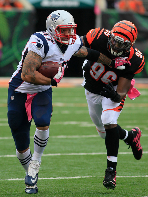 . Cincinnati Bengals defensive end Carlos Dunlap (96) pursues New England Patriots tight end Michael Hoomanawanui (47) in the first half of an NFL football game onSunday, Oct. 6, 2013, in Cincinnati. (AP Photo/Tom Uhlman)