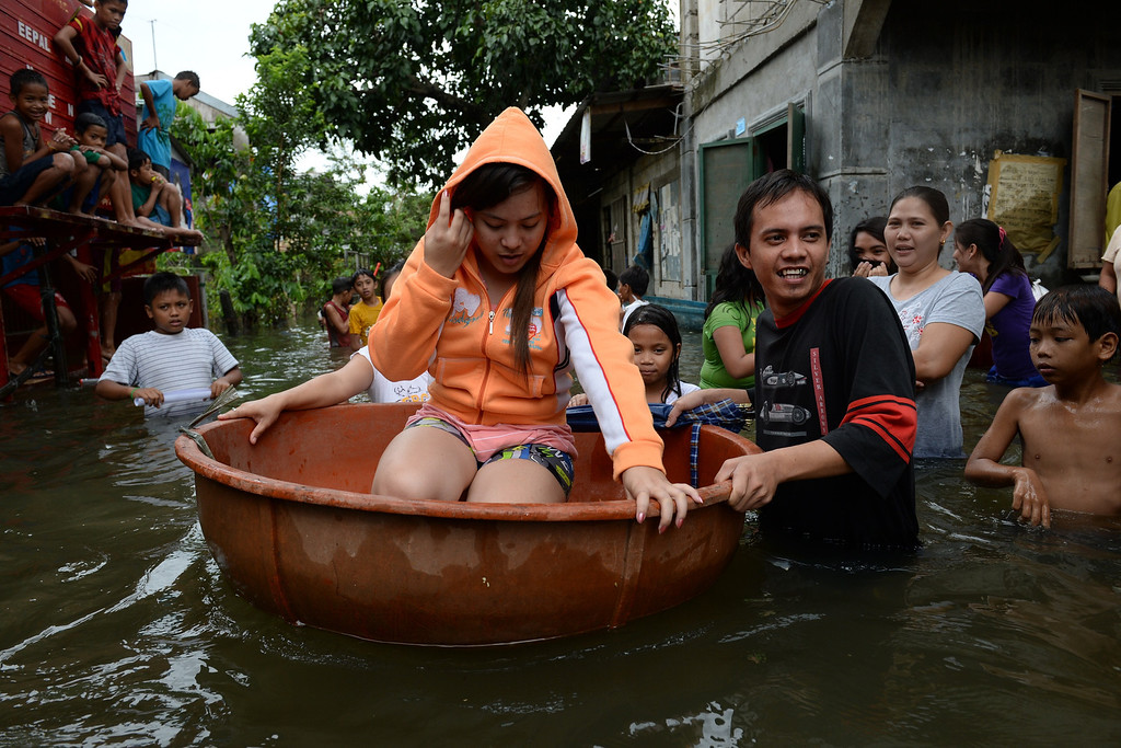 . A woman, one of the thousands affected by flooding due to heavy rains exarcebated by Tropical storm Trami, is transported in a makeshift boat along a flooded street in the town of Calumpit, Bulacan province, north of Manila on August 22, 2013. Disaster-weary Philippine residents mopped up August 22 after four days of rains that officials said had killed 18 people and forced more than half a million from flooded homes. TED ALJIBE/AFP/Getty Images