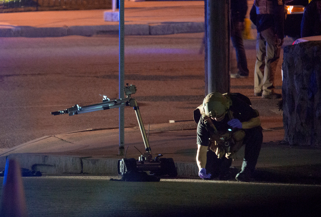 . A Police official looks over object that was picked up by a remote control device, left, as they investigate an incident in Friday, April 19, 2013, in Watertown, Mass. in which shots were reported to have been fired. (AP Photo/Craig Ruttle)