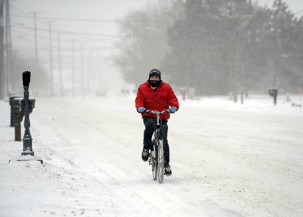 . Jordan Beaudrie rides his bike in the snow in St. Clair Shores, Mich., Thursday, Jan. 2, 2014.   A multi-day storm dropped up to a foot of snow on parts of Michigan, causing crashes and spinouts on roadways. Snowfall began Tuesday and continued Thursday morning. (AP Photo/Detroit News,  David Coates)