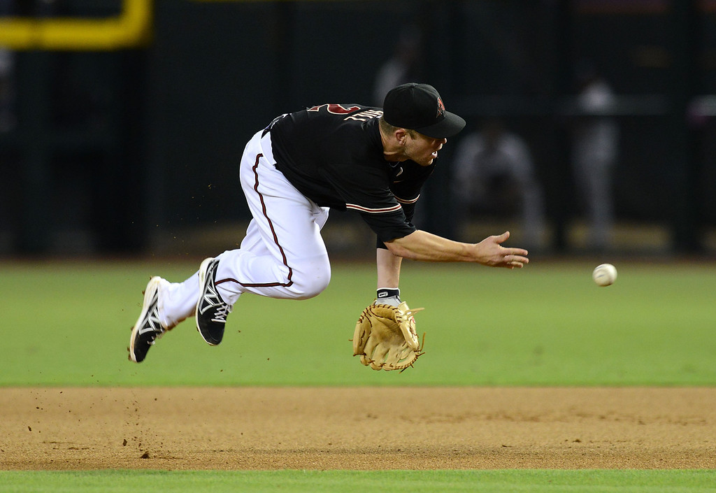 . PHOENIX, AZ - JULY 06:  Aaron Hill #2 of the Arizona Diamondbacks makes an underhand toss to first base against the Colorado Rockies at Chase Field on July 6, 2013 in Phoenix, Arizona.  (Photo by Norm Hall/Getty Images)