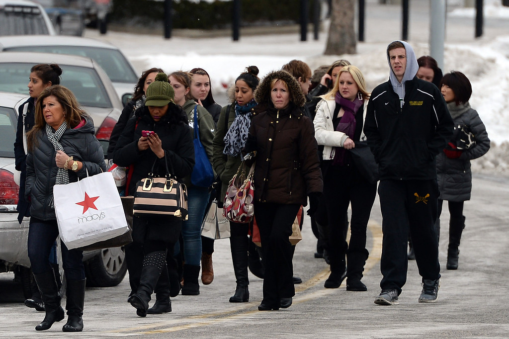 . People walk outside of Columbia Town Center Mall after three people were killed in a shooting there January 25, 2014 in Columbia, Maryland. Police still do not have a motive for the shooting but believe the shooter has been killed. (Photo by Patrick Smith/Getty Images)