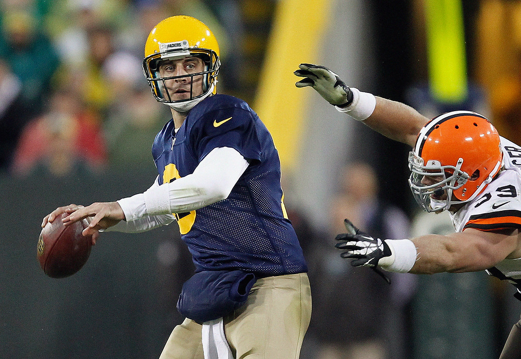 . Green Bay Packers\' Aaron Rodgers looks to pass as Cleveland Browns\' Paul Kruger applies pressure during the second half of an NFL football game Sunday, Oct. 20, 2013, in Green Bay, Wis. (AP Photo/Mike Roemer)