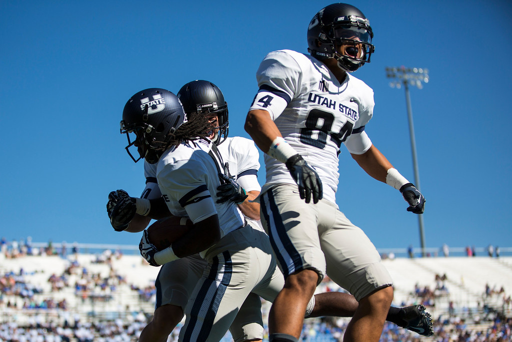 . Utah State players celebrate in the end zone after wide receiver Ronald Butler scored a touchdown during an NCAA college football game against Air Force, Saturday, Sept. 7, 2013, in Air Force Academy, Colo. Utah State won 52-20. (AP Photo/The Gazette, Kent Nishimura)