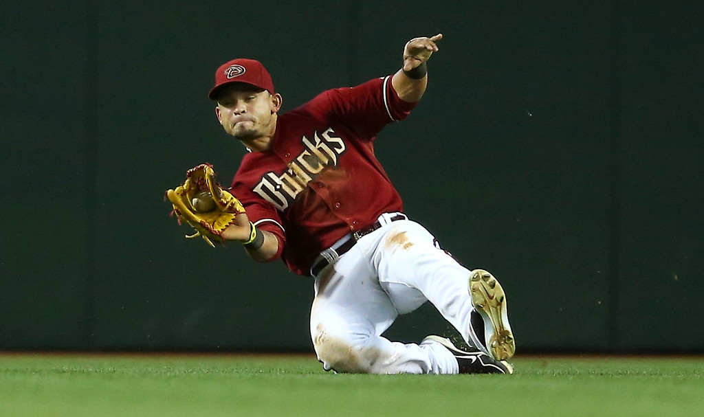 . Outfielder Gerardo Parra #8 of the Arizona Diamondbacks makes a sliding catch on a fly ball hit by Nolan Arenado (not pictured) of the Colorado Rockies during the seventh inning of the MLB game at Chase Field on April 28, 2013 in Phoenix, Arizona.  (Photo by Christian Petersen/Getty Images)