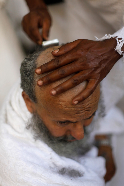 """. Saudi Muslim pilgrim, Saud al Kahtani,  has his head ritually shaved after he cast stones at a pillar, symbolizing the stoning of Satan, in a ritual called \""""Jamarat,\"""" a rite of the annual hajj, in the Mina neighborhood of Mecca, Saudi Arabia, Tuesday, Oct. 15, 2013. The 10th day of the Islamic lunar month of Dhul-Hijja, during the hajj, is the beginning of Eid al-Adha, the most important Islamic holiday, to mark the willingness of the Prophet Ibrahim, or Abraham to Christians and Jews, to sacrifice his son. (AP Photo/Amr Nabil)"""