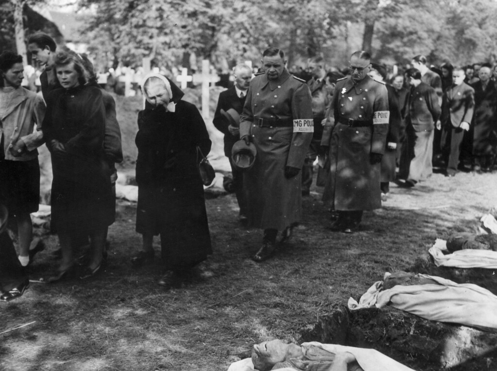 . 7th May 1945:  German police and citizens of Ludwigslust file past bodies of inmates of nearby Wobbelin concentration camp. The bodies have been exhumed from a mass grave and are to be reburied in the town.  (Photo by Hulton Archive/Getty Images)