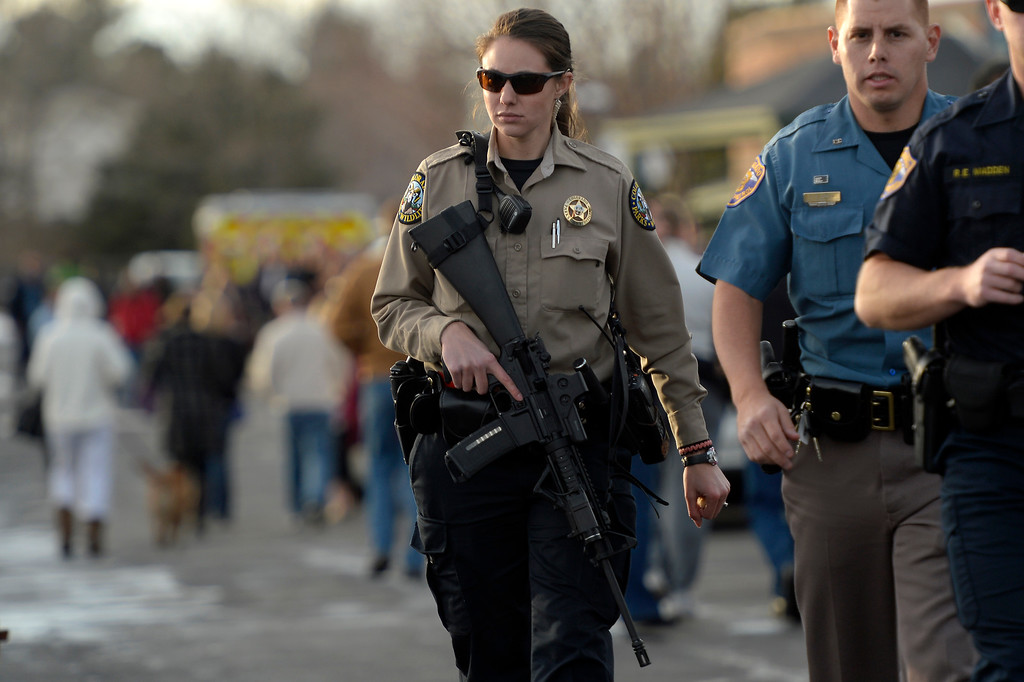. CENTENNIAL, CO. - December 13: Officers in the parking lot as kids are bussed to Shepherd of the Hills church during a lockdown when a student carried a shotgun into Arapahoe High School and opened fire on Friday, wounding two fellow students before apparently killing himself December 13, 2013 Centennial, CO. (Photo By Joe Amon/The Denver Post)