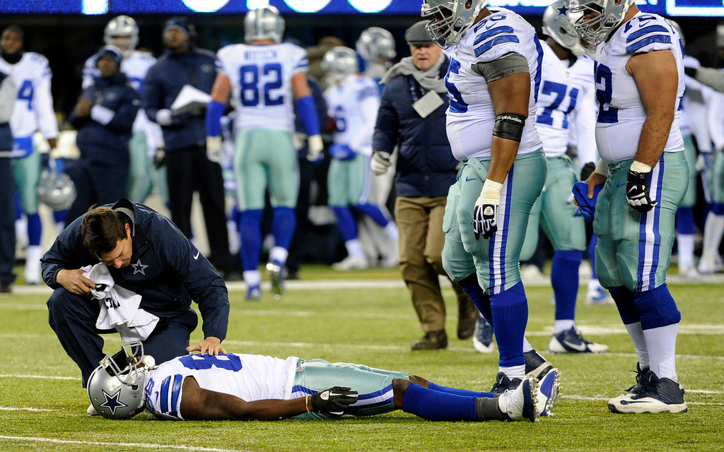 . A trainer looks at Dallas Cowboys wide receiver Dez Bryant after he was hurt on a play against the New York Giants during the first half of an NFL football game Sunday, Nov. 24, 2013, in East Rutherford, N.J. (AP Photo/Bill Kostroun)