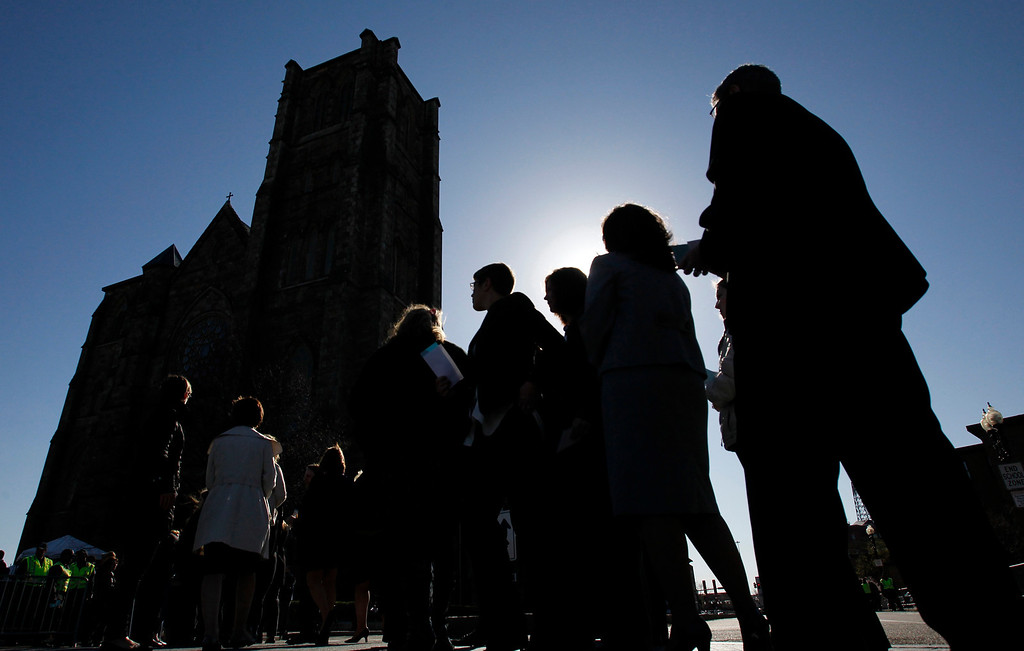 . People queue for security check outside the Cathedral of the Holy Cross where U.S. President Barack Obama is scheduled to attend an interfaith service for the victims of the Boston Marathon bombings in Boston, Massachusetts April 18, 2013. Obama was due to visit Boston on Thursday to attend a memorial service for victims of the Boston Marathon bombing amid a manhunt for a suspect seen on video taken before two blasts struck near the finish line on Monday.  REUTERS/Jessica Rinaldi
