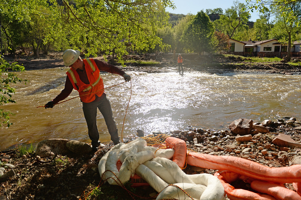 . Crews with Ecoos Environmental and Disaster Restoration tie floats to catch debris if they go into the river as they work on demolishing a home in Lyons that was damaged by last years flood, May 27, 2014. (Photo by RJ Sangosti/The Denver Post)
