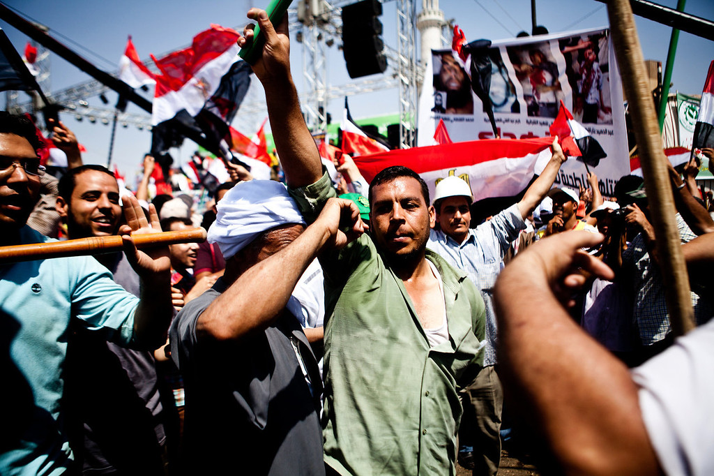 . Men chant and dance with sticks and national flags at a rally to support Egyptian President Mohammed Morsi in Nasser City, Cairo, Sunday, June 30, 2013. Thousands of opponents and supporters of Egypt\'s Islamist president began massing in city squares in competing rallies Sunday, gearing up for a day of massive nationwide protests that many fear could turn deadly as the opposition seeks to push out Mohammed Morsi.  (AP Photo/Virginie Nguyen Hoang)