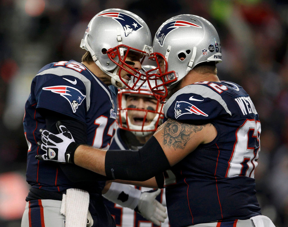 . New England Patriots quarterback Tom Brady (L) celebrates his first half touchdown pass against the Baltimore Ravens with center Ryan Wendell (62) during the NFL AFC Championship football game in Foxborough, Massachusetts, January 20, 2013. REUTERS/Adam Hunger