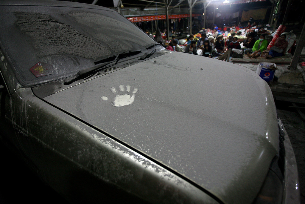 . A hand print is seen on the hood of a car covered with volcanic ash from the eruption of Mount Sinabung that falls in Tiga Nderket village, North Sumatra, Indonesia,Monday Nov. 4, 2013. The 2,600-meter (8,530-foot) high volcano has been erupting since Sunday, unleashing volcanic ash high into the sky and forcing the evacuation of villagers living around its slopes. (AP Photo/Binsar Bakkara)