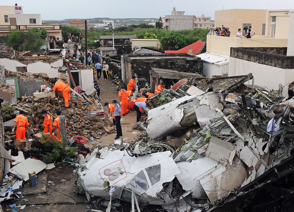 . Rescue workers and firefighters search through the wreckage where TransAsia Airways flight GE222 crashed the night before near the airport at Magong on the Penghu island chain on July 24, 2014.   AFP PHOTO / Sam YehSAM YEH/AFP/Getty Images