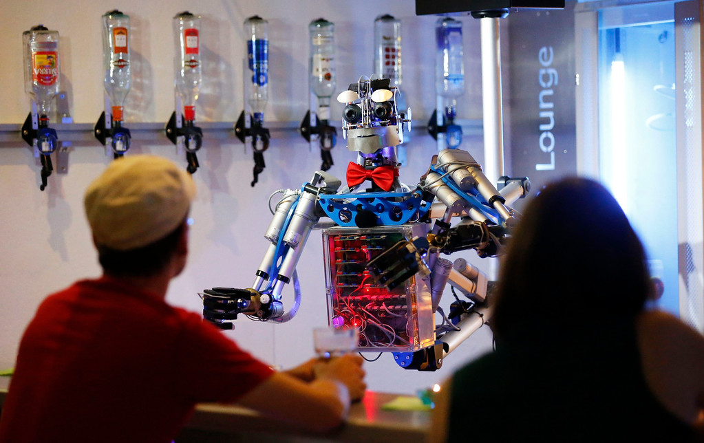 """. Humanoid robot bartender \""""Carl\"""" interacts with guests at the Robots Bar and Lounge in the eastern German town of Ilmenau, July 26, 2013. \""""Carl\"""", developed and built by mechatronics engineer Ben Schaefer who runs a company for humanoid robots, prepares spirits for the mixing of cocktails and is able to interact with customers in small conversations. Picture taken July 26, 2013. REUTERS/Fabrizio Bensch"""