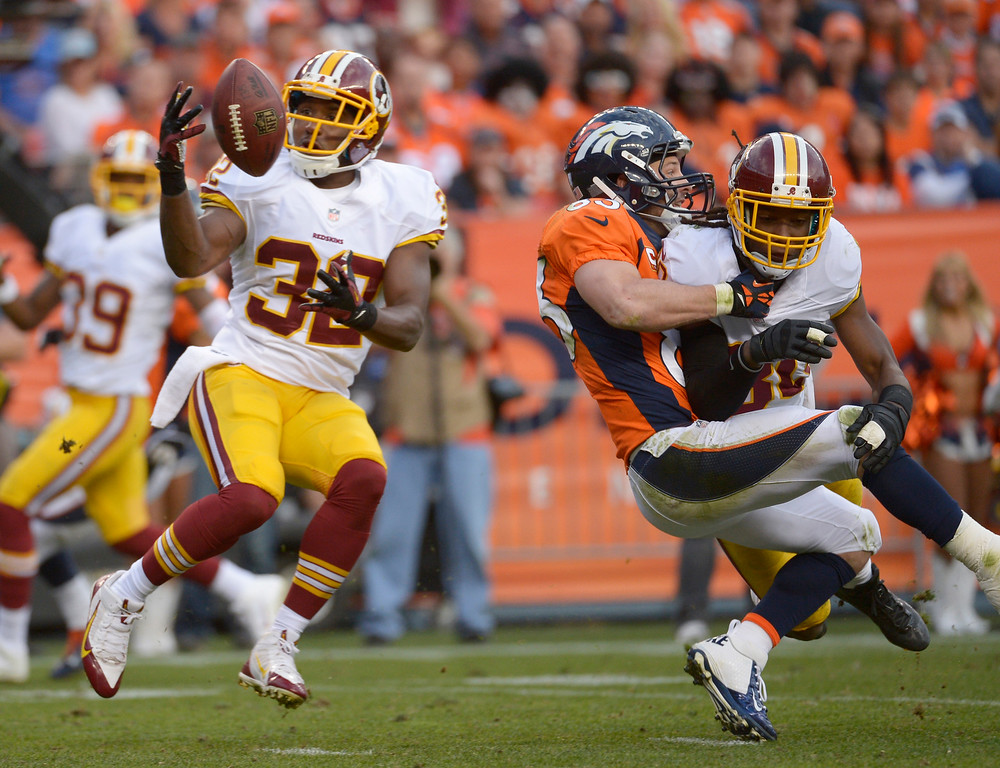 . Denver Broncos defensive back Tony Carter (32) catches the ball for a interception as Denver Broncos wide receiver Wes Welker (83) falls to the turf.   (Photo by Tim Rasmussen/The Denver Post)
