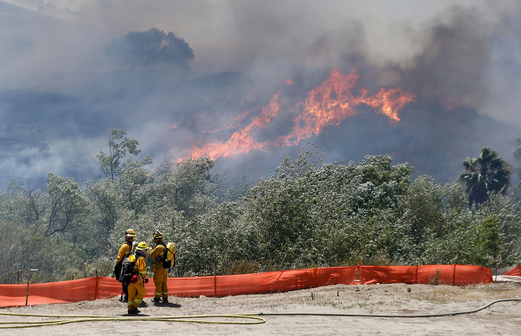 . Flames grow as a wild fire burns out-of-control in the north county area of San Diego Tuesday, May 13, 2014, in San Diego.   (AP Photo)