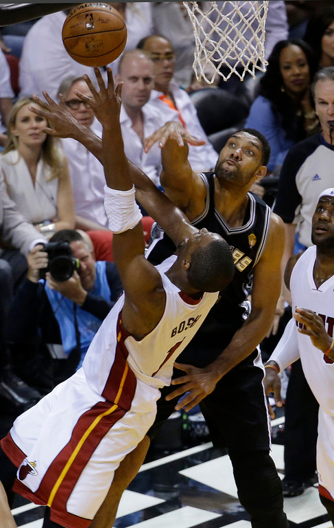 . San Antonio Spurs forward Tim Duncan (21) blocks a shot to the basket by Miami Heat center Chris Bosh (1), during the first half in Game 4 of the NBA basketball finals, Thursday, June 12, 2014, in Miami.  (AP Photo/Wilfredo Lee)