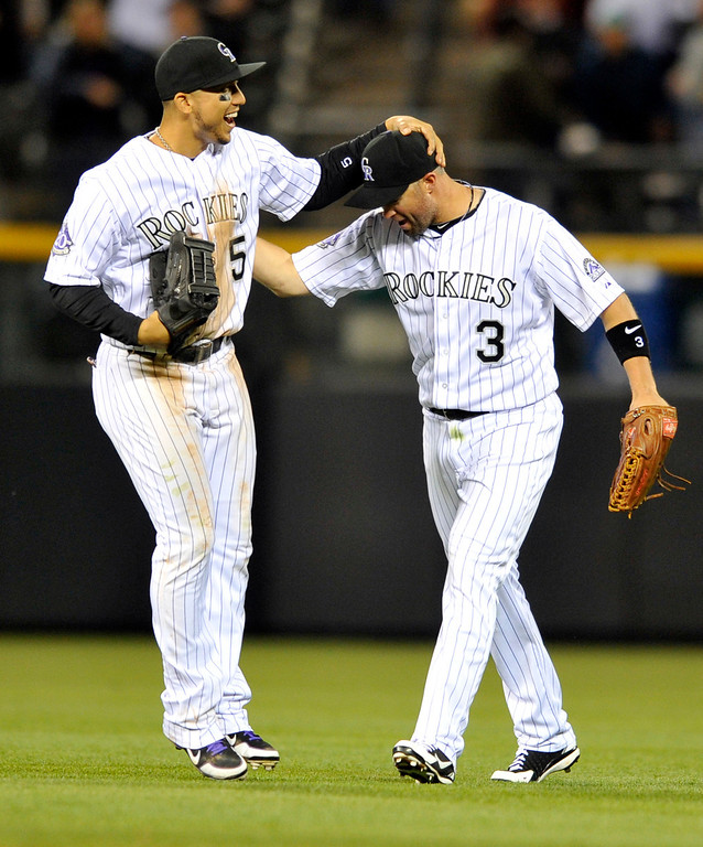 . Colorado Rockies left fielder Carlos Gonzalez (5) and right fielder Michael Cuddyer (3) celebrate a 6-3 victory over the San Diego Padres following a baseball game on Saturday, April 6, 2013, in Denver. (AP Photo/Jack Dempsey)