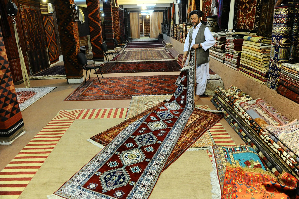. In this picture taken on June 3, 2014, an Afghan shopkeeper displays a carpet at his shop in part of Herat\'s old city. AFP PHOTO/Aref Karimi/AFP/Getty Images