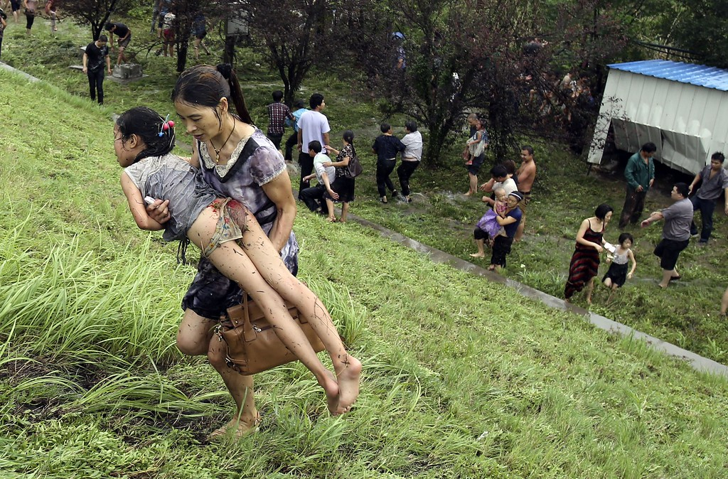 ". This picture taken on August 22, 2013 shows a woman carrying an injuried girl after they were washed down a hill from huge waves from the ""Haining tide\"" - a daily occurrence when the river tides hit the banks of the city - after a wave surged higher than usual due to the influence of Typhoon Trami in the region in Haining, in eastern China\'s Zhejiang province.      AFP PHOTOSTR/AFP/Getty Images"