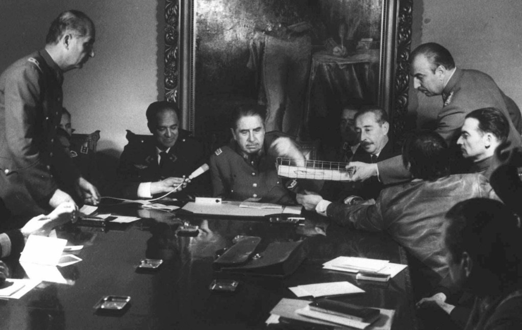 . In this Sept. 20, 1973 file photo, Gen. Augusto Pinochet, center, presides over a meeting with his military staff in Santiago, Chile, days after seizing power from President Salvador Allende. As Chile marks the 40th anniversary of the military coup on Wednesday Sept. 11, 2013 that was led by Pinochet, Allende\'s legacy is thriving. A socialist is poised to reclaim the presidency and a new generation, born after the return to democracy in 1990 has taken to the streets in vast numbers to demand the sort of social goals Allende promoted. (AP Photo/File)