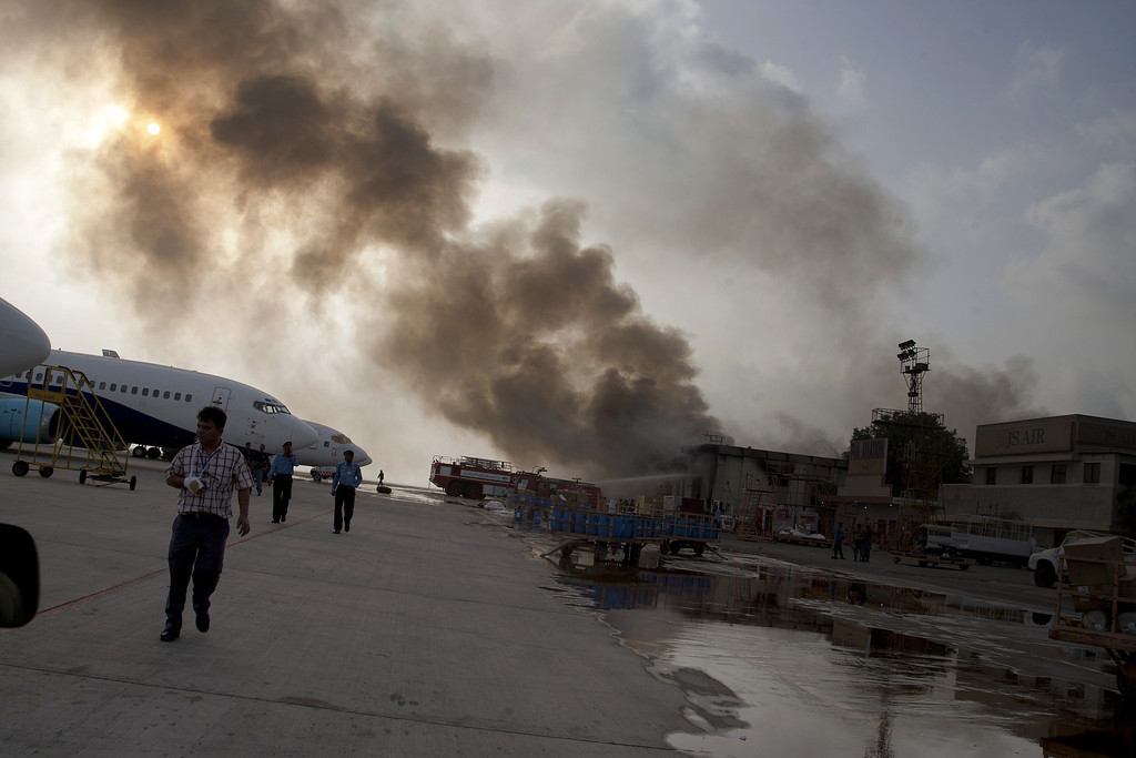 . Smoke rises above the Jinnah International Airport where security forces continue to battle militants Monday, June 9, 2014, in Karachi, Pakistan.  (AP Photo/Shakil Adil)