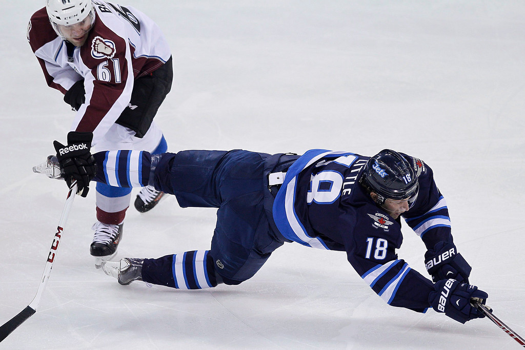 . Colorado Avalanche\'s Andre Benoit (61) trips Winnipeg Jets\' Bryan Little (18) during the first period of an NHL hockey game Wednesday, March 19, 2014, in Winnipeg, Manitoba. (AP Photo/The Canadian Press, John Woods)