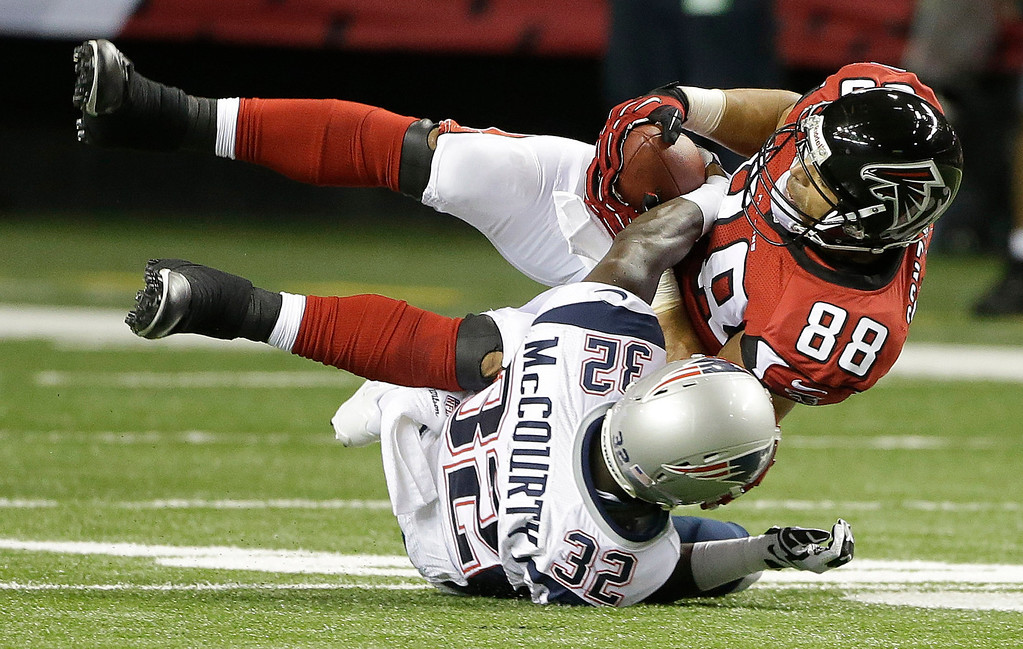 . Atlanta Falcons tight end Tony Gonzalez (88) is hit by New England Patriots free safety Devin McCourty (32) during the first half of an NFL football game, Sunday, Sept. 29, 2013, in Atlanta. (AP Photo/John Bazemore)